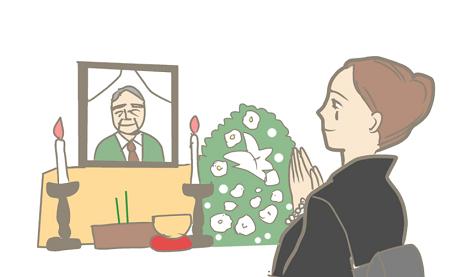 お葬式で手を合わせる喪服の女性